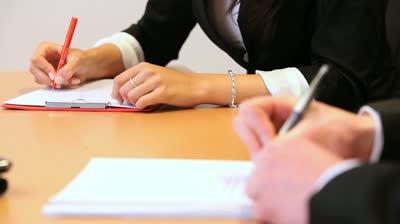 stock footage woman writing on a piece of paper with a red pen Sefii unei banci, retinuti pentru abuz in serviciu